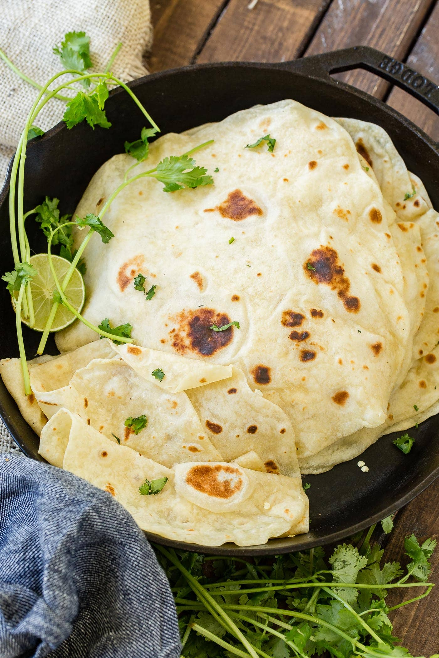 A photo of a stack of cooked homemade flour tortillas in a cast iron skillet.
