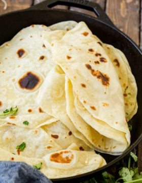 A photo of a stack of cooked homemade flour tortillas in a cast iron skillet with the top few tortillas folded in half.
