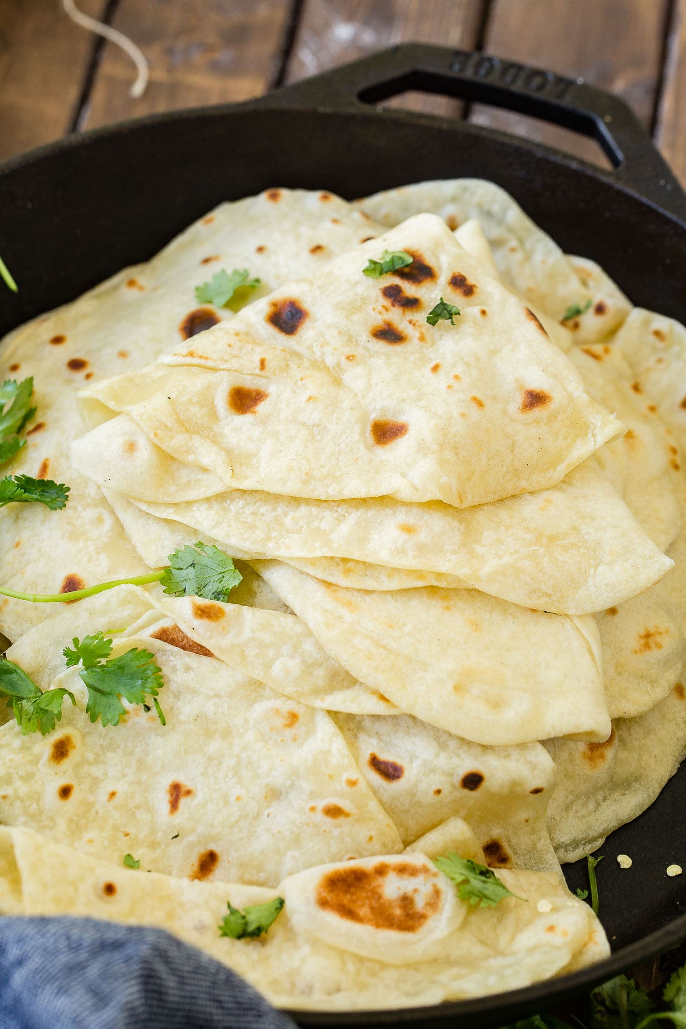 A photo of a stack of cooked homemade flour tortillas in a cast iron skillet with the top few tortillas folded in quarters.