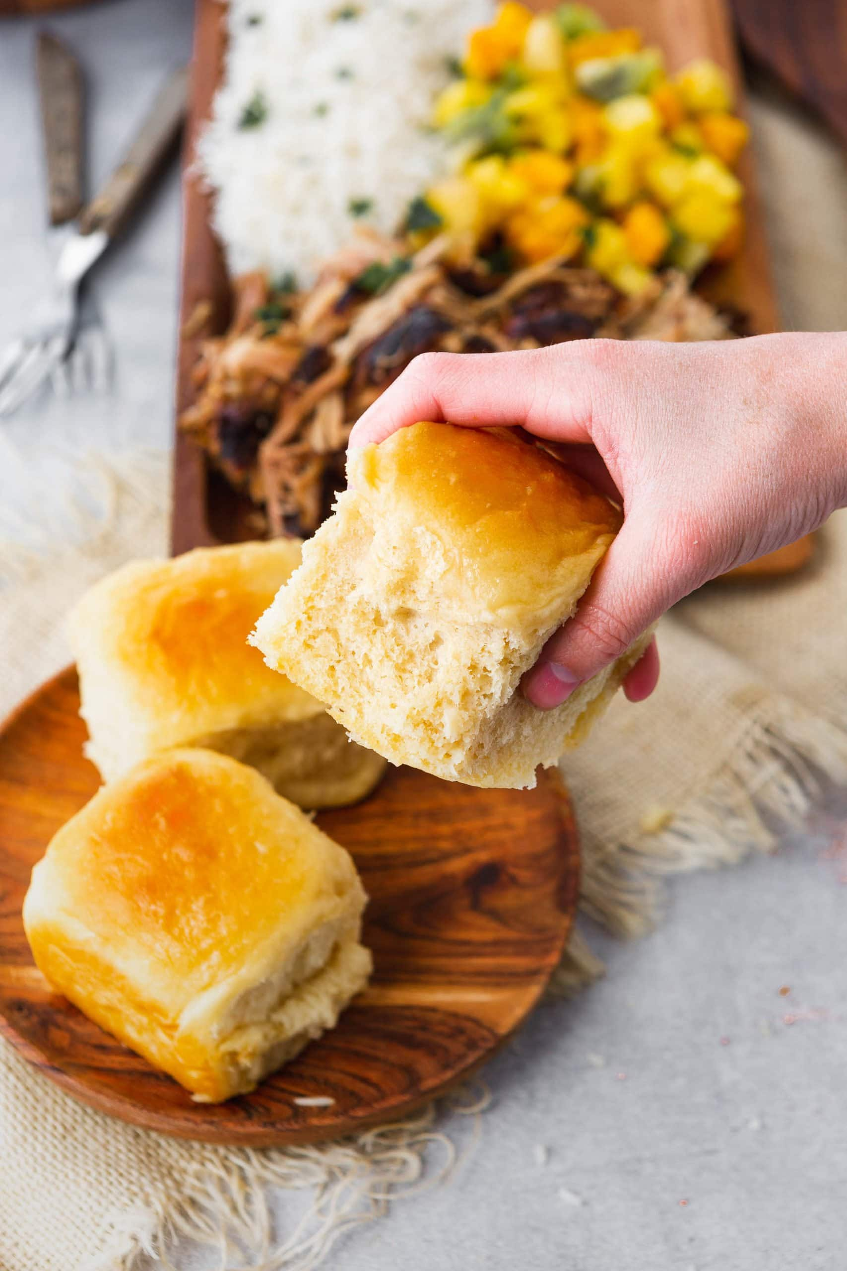 a photo of a soft hawaiian roll being picked up from a wooden plate with two other rolls on it.