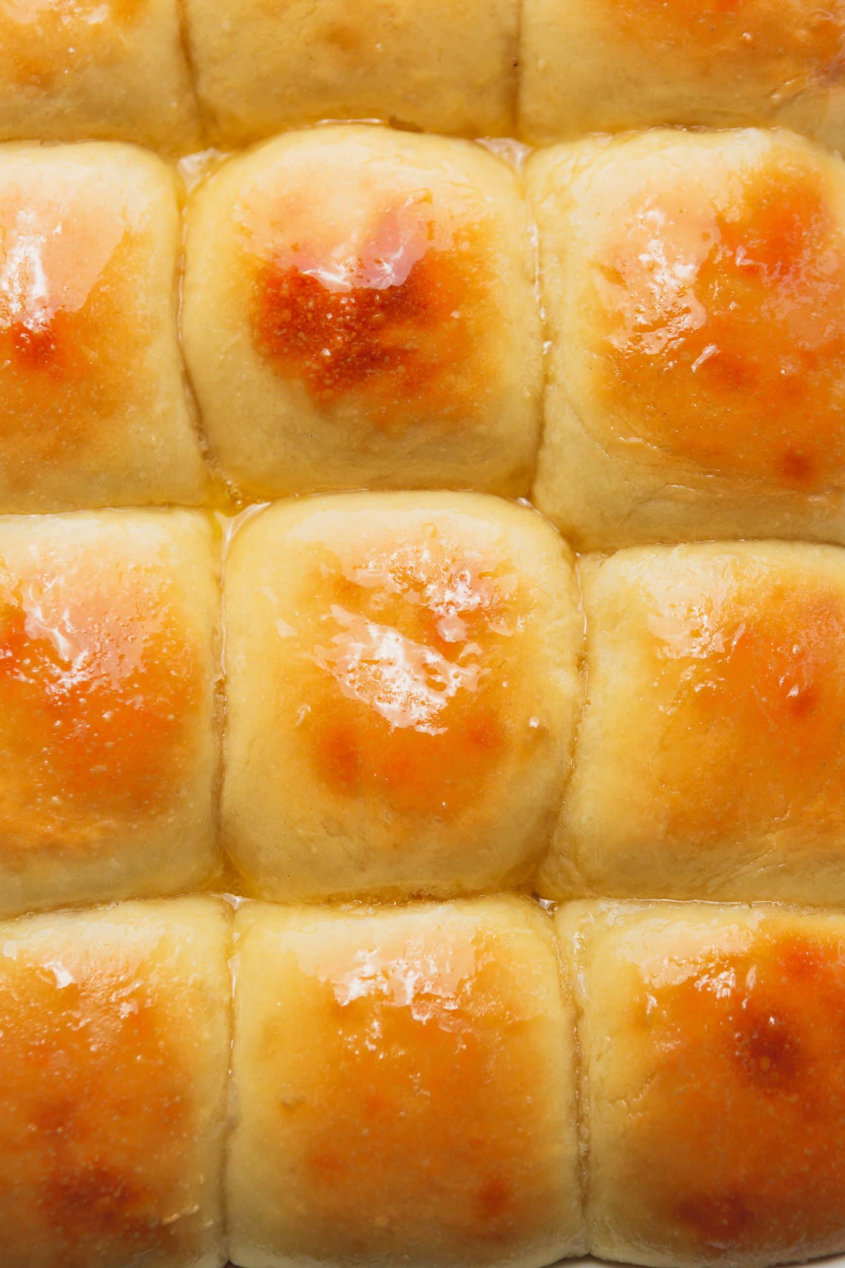 Picture of a pan filled with well-baked Hawaiian rolls topped with melted butter