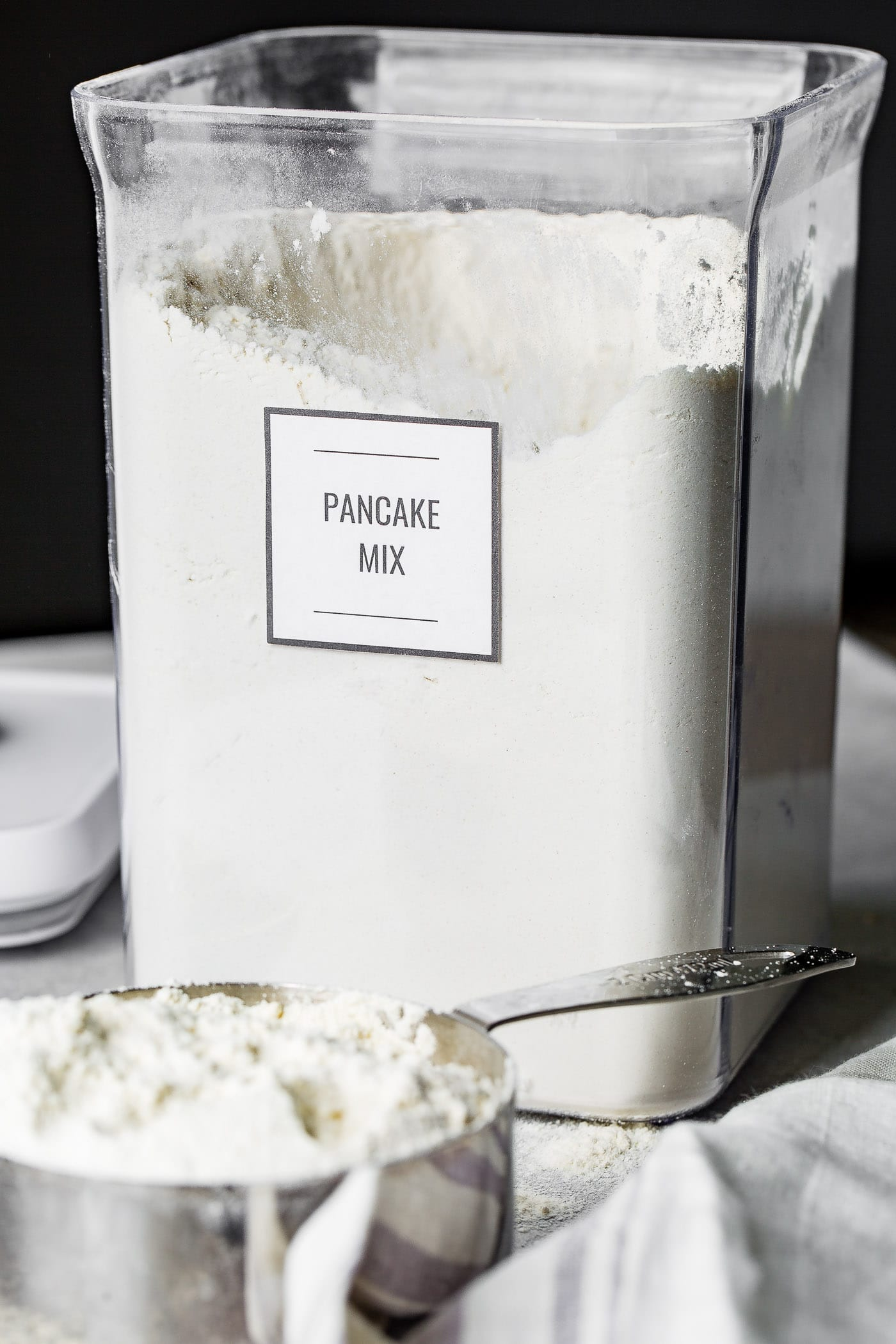 A clear canister containing buttermilk pancake mix. The lid to the canister is laying next to the canister, and a heaping cup of pancake mix is in front of the canister.
