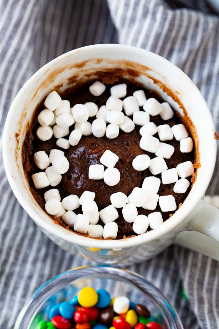 A photo of a white mug full of brownie topped with mini marshmallows..