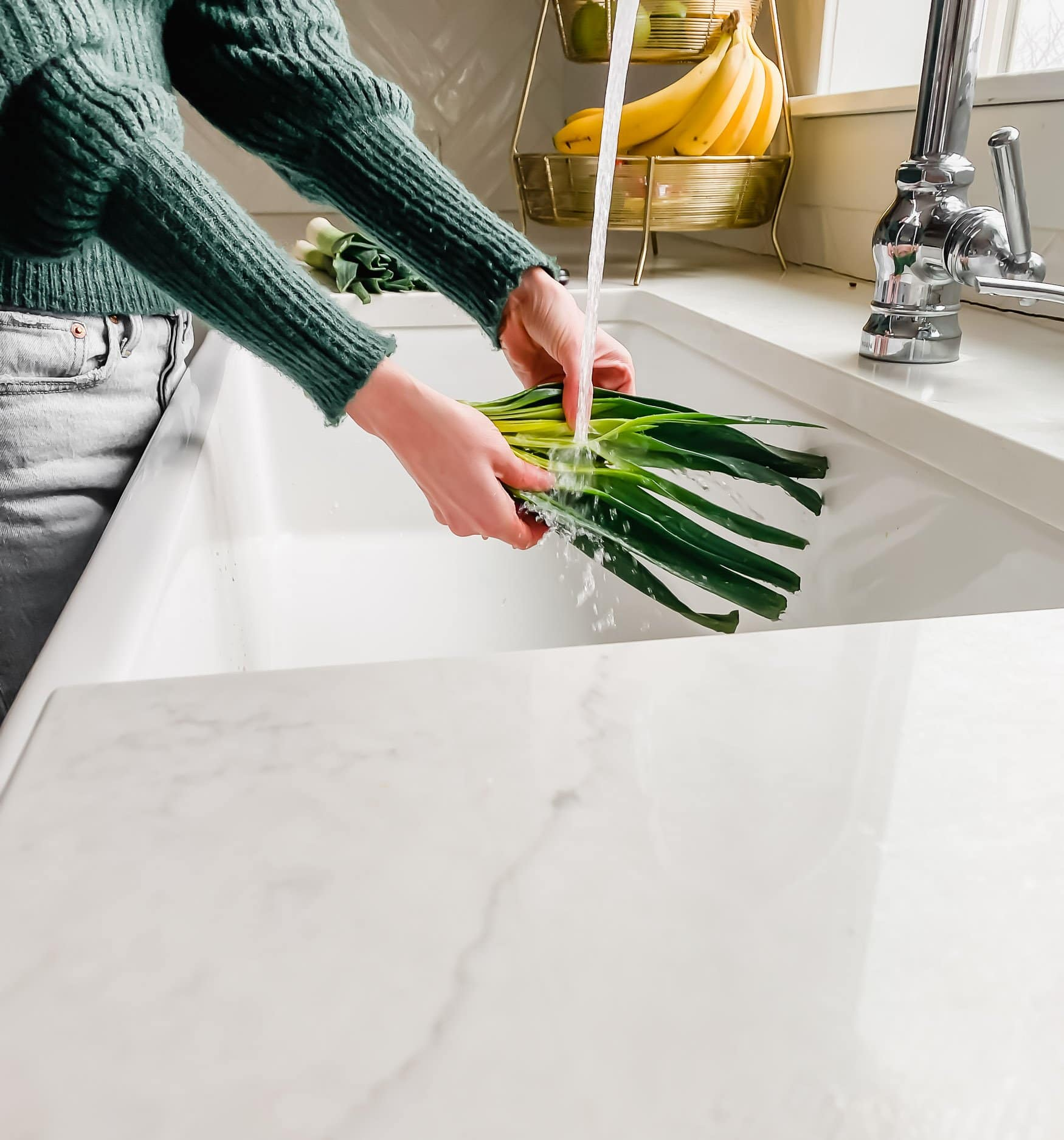 A photo of a womans hands cleaning leeks under a running faucet
