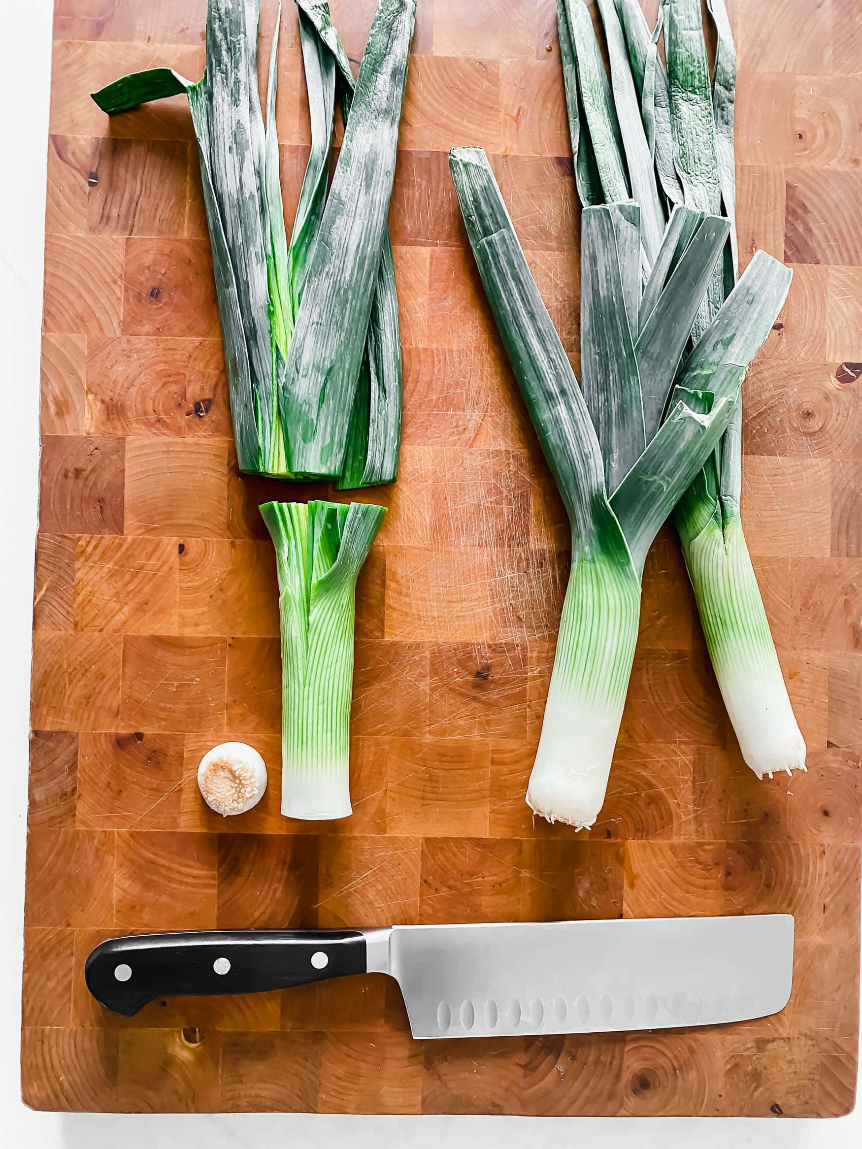 A photo of two leeks sitting side by side on a wooden cutting board. The top of one of the leeks has been cut off and a knife is laying on the cutting board next to them.