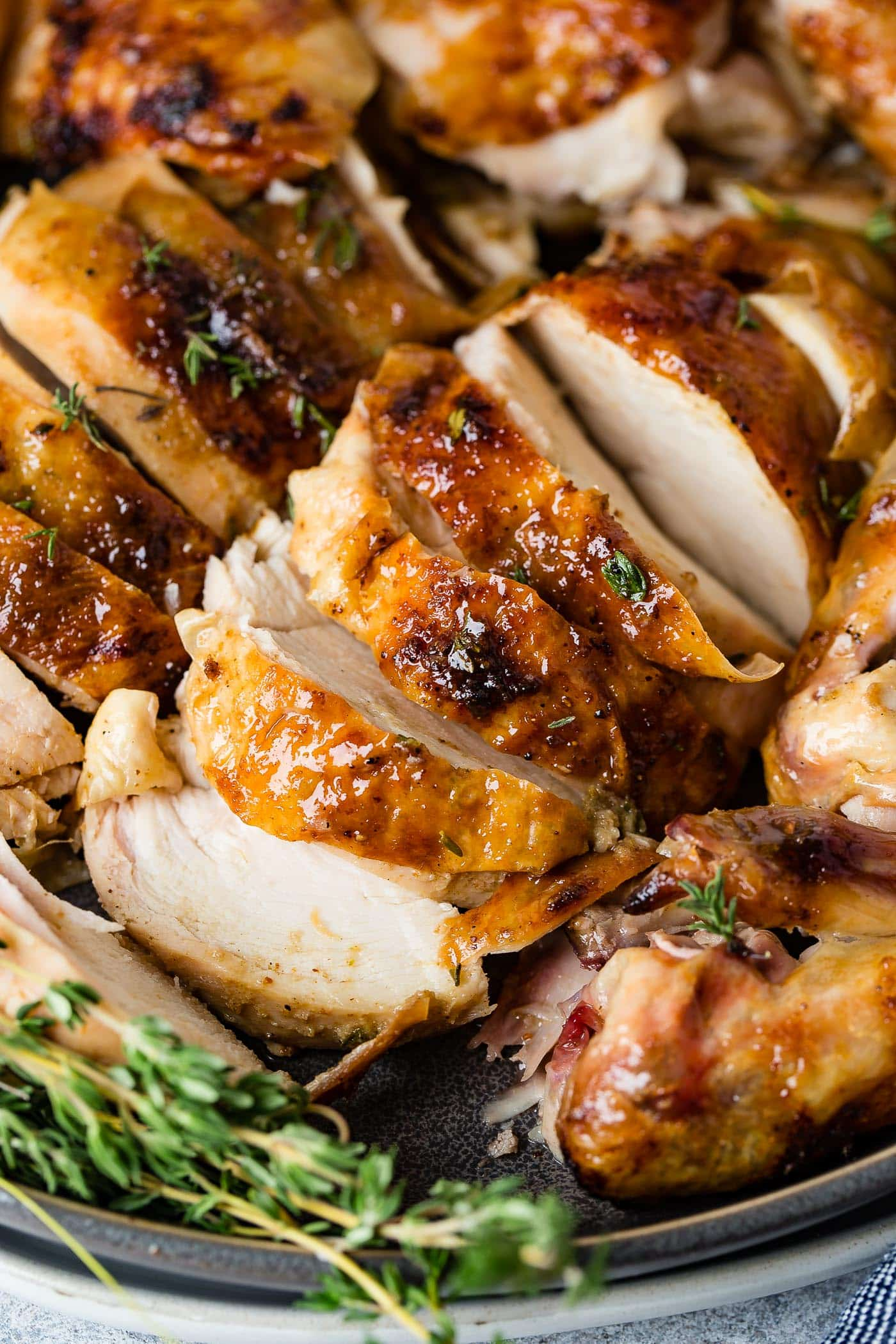 A sliced smoked chicken, with sprigs of fresh thyme next to the slices of chicken.