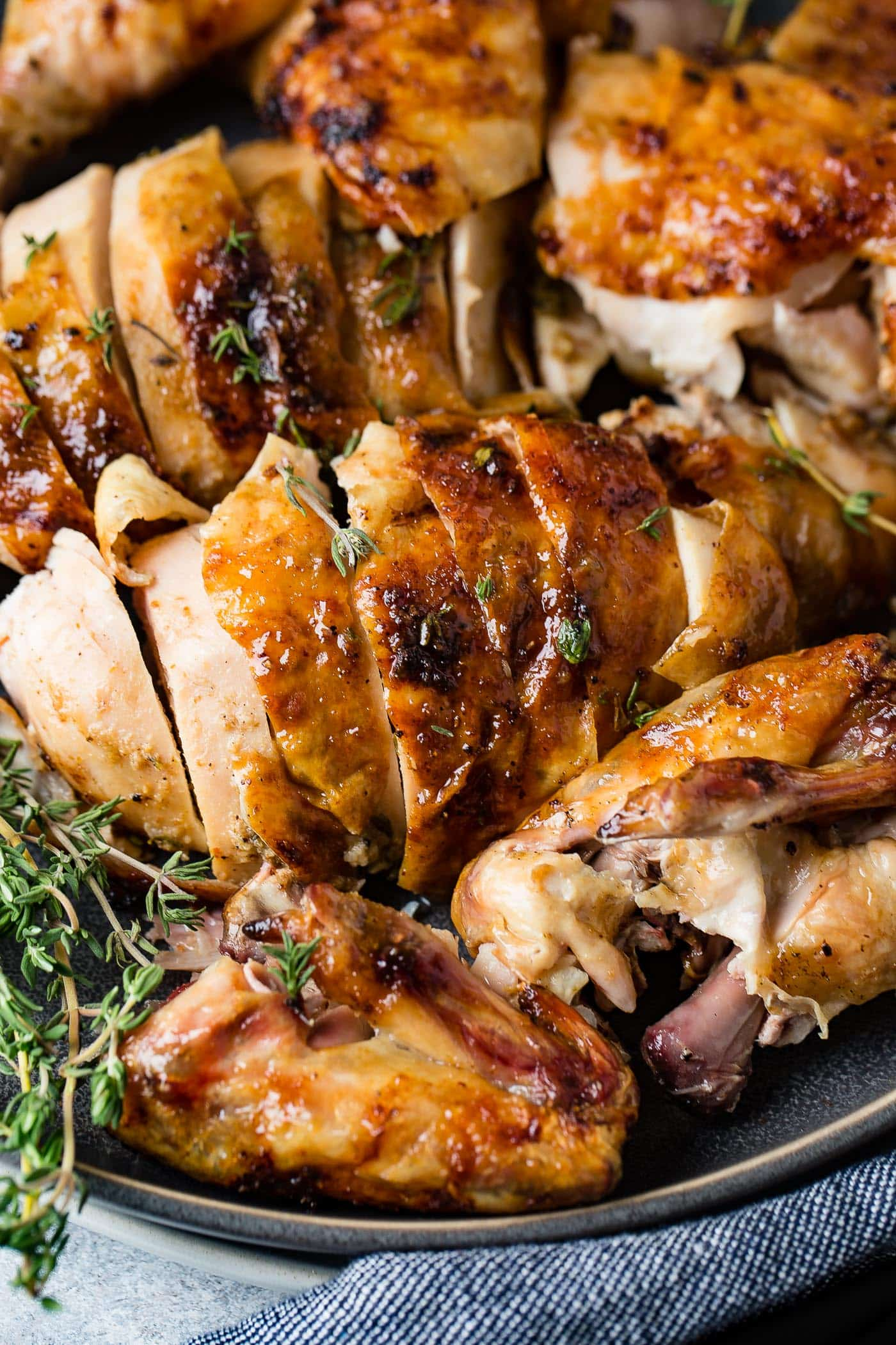 A sliced smoked chicken on a platter. There are fresh thyme leaves sprinkled over the top of the chicken and sprigs of thyme are on the platter.