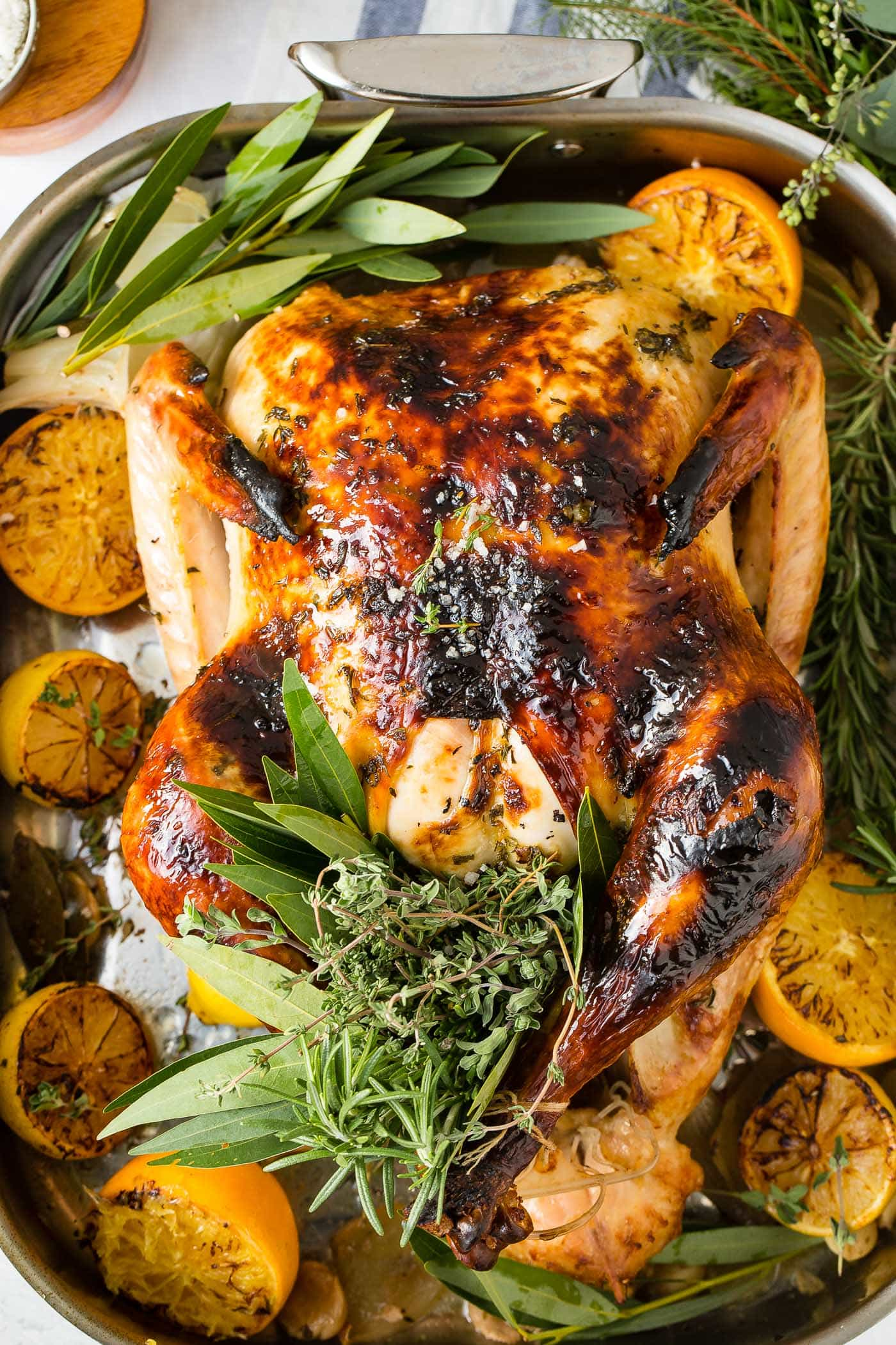 A photo of a whole roasted turkey on a platter surrounded by roasted lemon halves and bunches of fresh herbs.