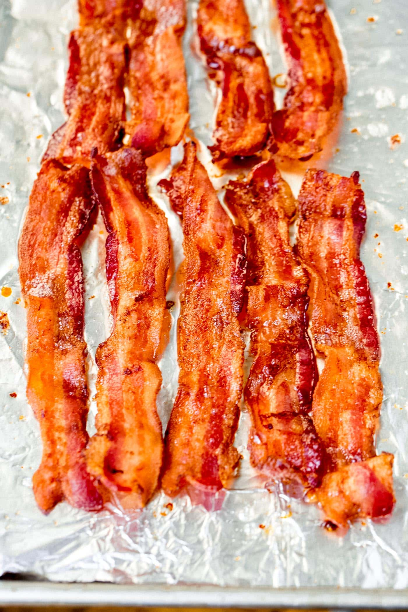 Slices of perfectly crisp bacon on a baking sheet lined with foil.