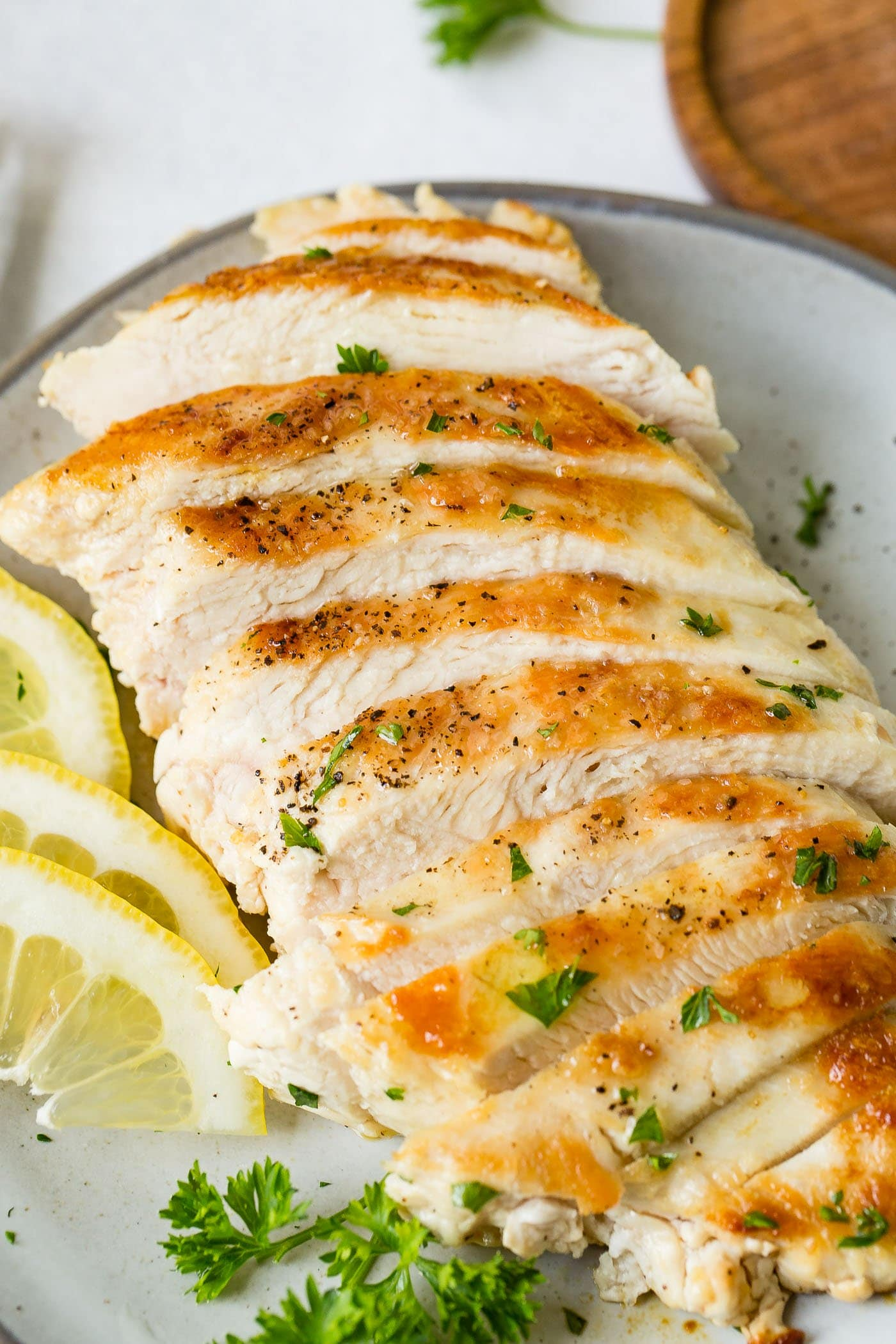 A perfectly cooked chicken breast that has been sliced.  There are slices of lemon next to the chicken and a few fresh parsley leaves are scattered on to of the chicken.