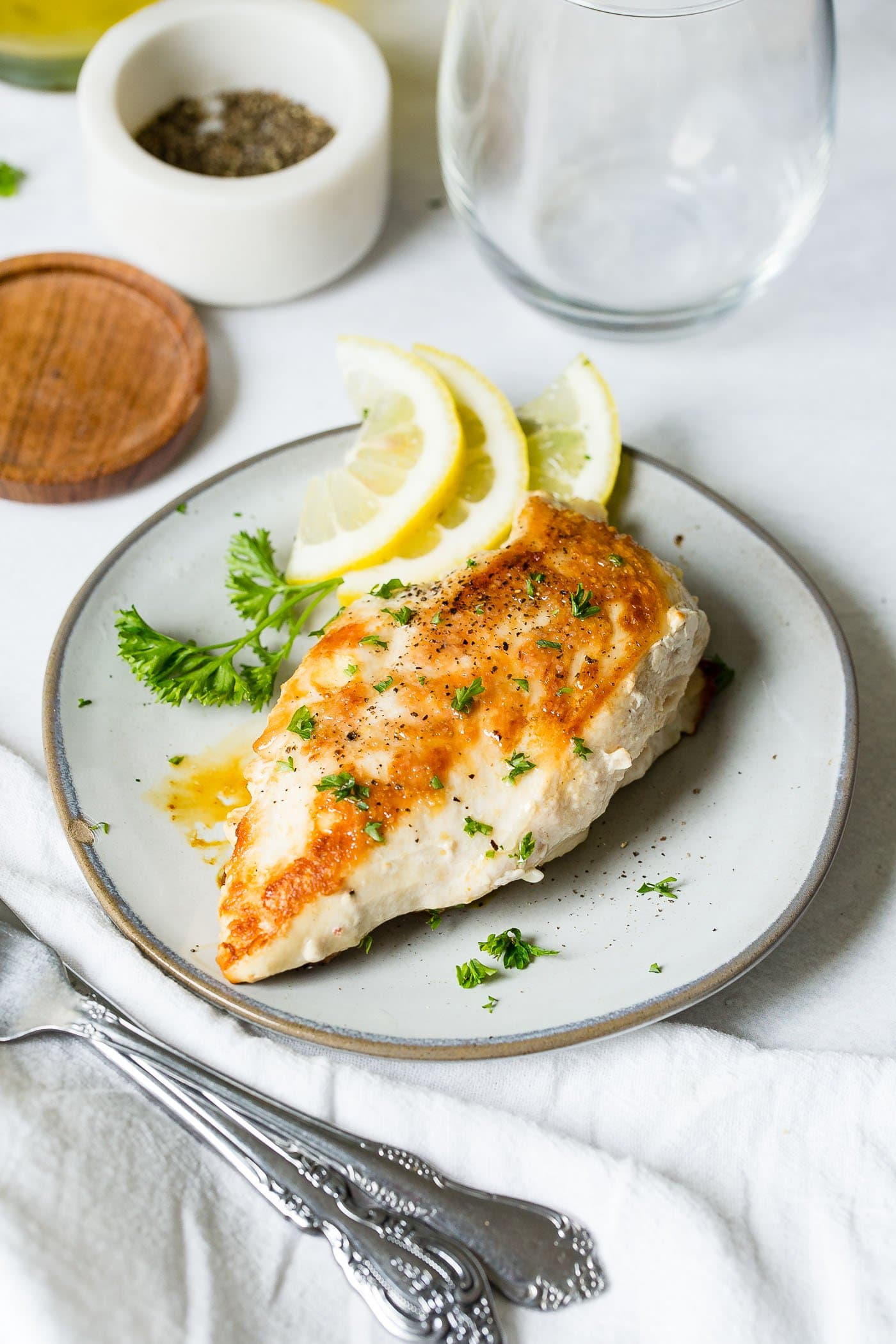 A perfectly cooked chicken breast on a white plate.  There are three slices of lemon and some fresh parsley next to the chicken.  A wooden coaster and salt and pepper are in the background.