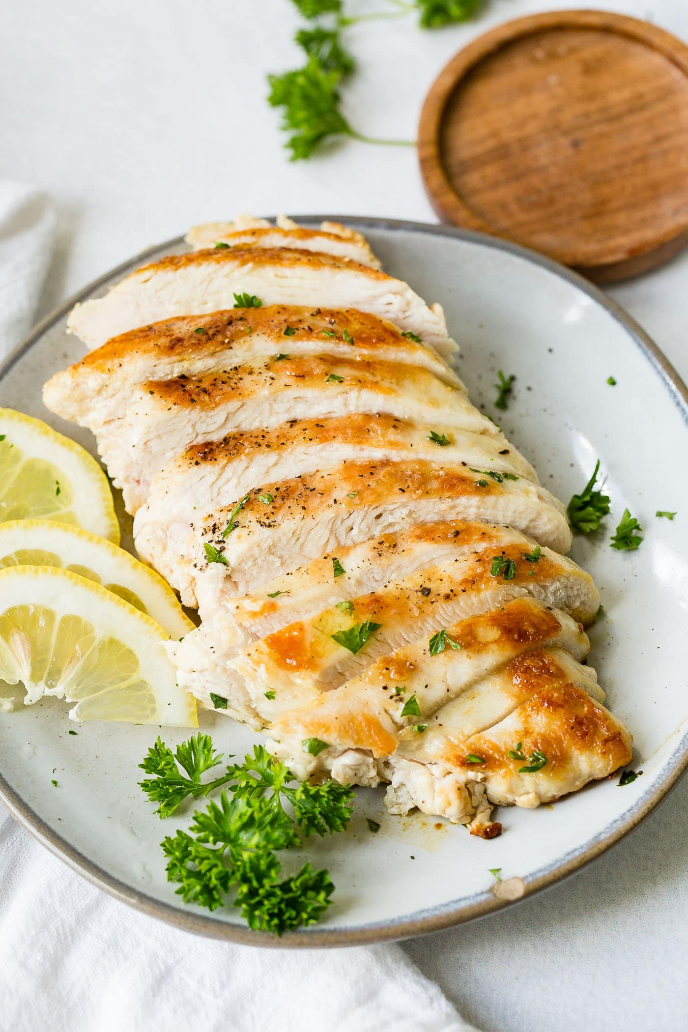 A white plate with a perfectly cooked chicken breast that has been sliced.  There are slices of lemon and a little fresh parsley next to the chicken.