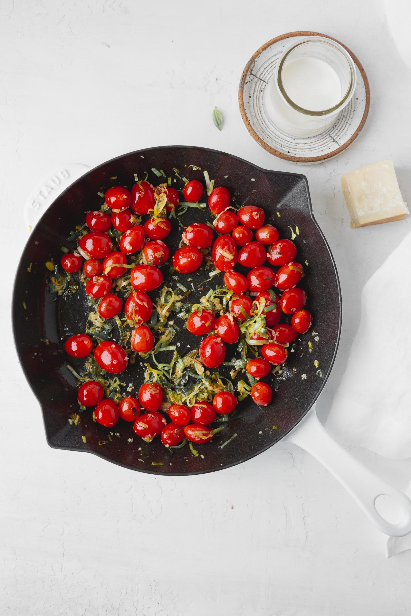 A photo of a skillet with fresh cherry tomatoes and sliced leeks all ready to cook.