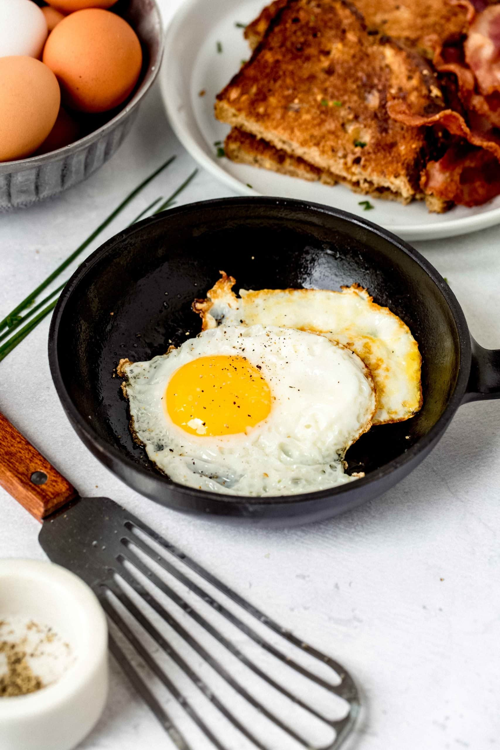 Two fried eggs in a small black frying pan. A spatula is in front of the pan and a plate of toast and some brown eggs are in the background.