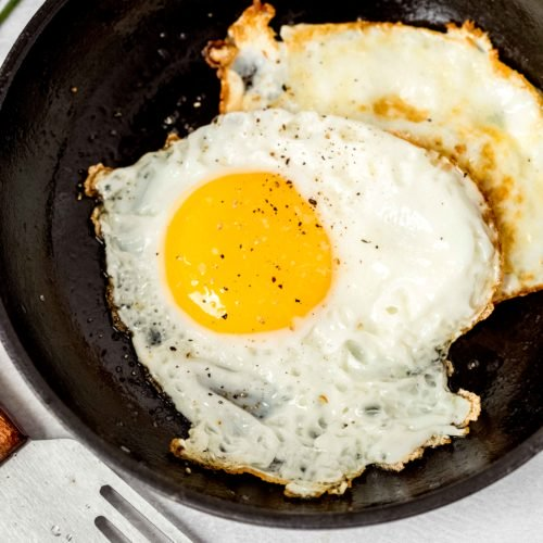 Two fried eggs in a small black frying pan. A spatula is on the table next to the frying pan.