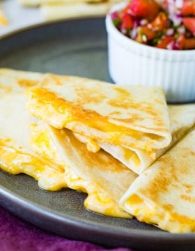 A photo of the best quesadilla sliced into pieces and stacked on each other with cheesy oozing out and a bowl of fresh pico de gallo in the background.