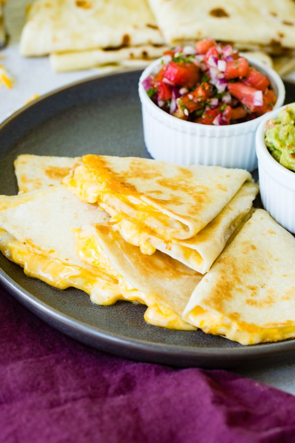 A photo of the best quesadilla sliced into pieces and stacked on each other with cheesy oozing out and a bowl of fresh pico de gallo and bowl of guacamole in the background.