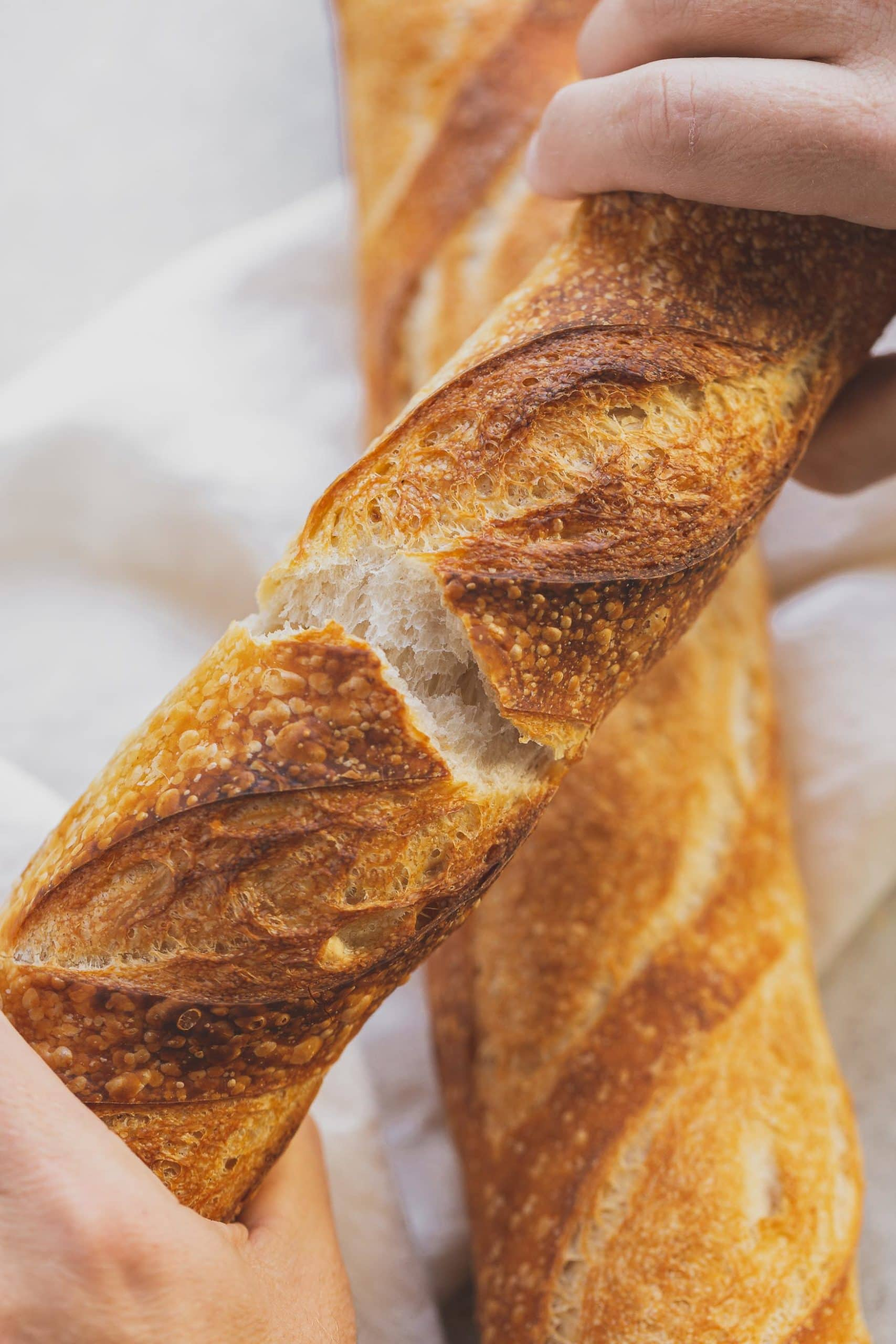 Two loaves of baguette bread. They are criss cross on top of each other, and the top loaf is broken to show the soft interior.