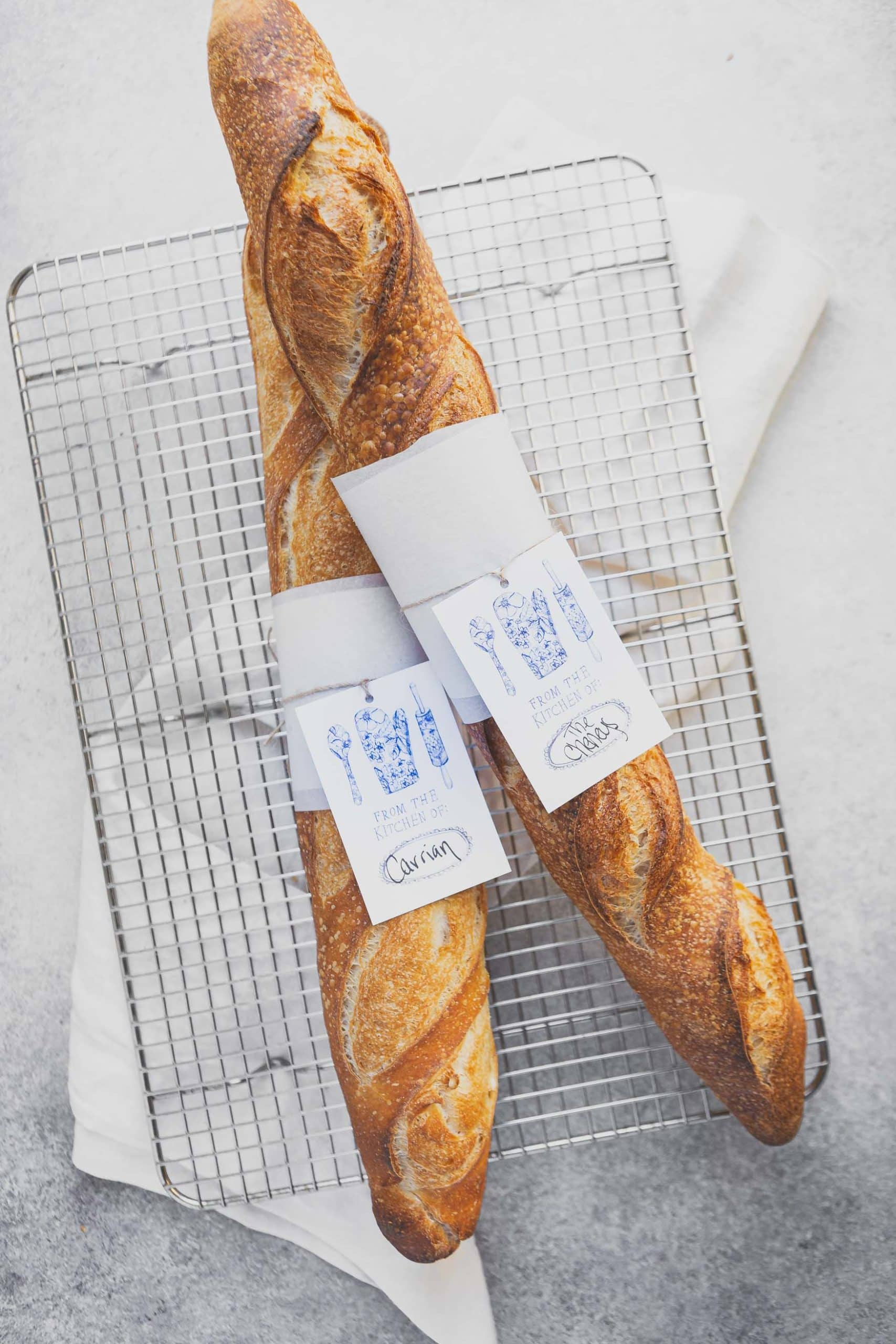 Two freshly baked baguettes on a cooling rack. The baguettes have a paper wrap and tag around the center of the loaf.
