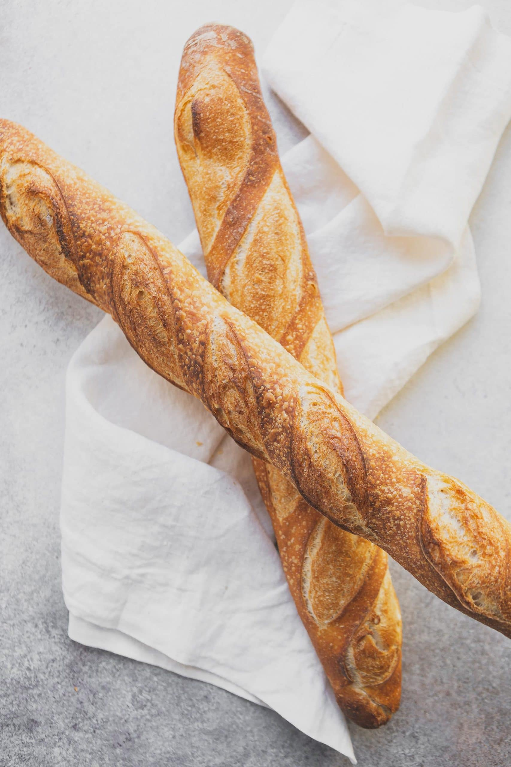 Two loaves of fresh baguettes on a white tea towel. They are baked to a golden brown.