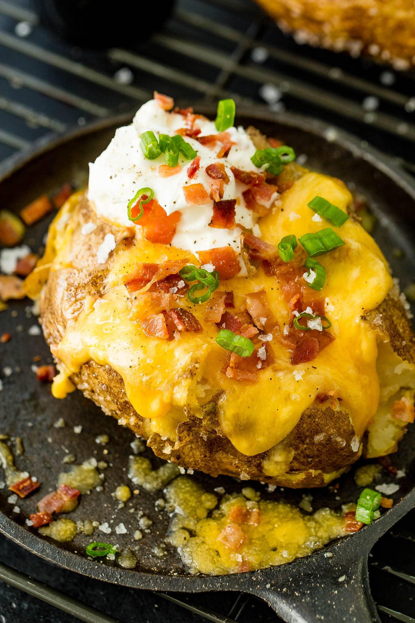 a loaded baked potato with cheese, sour cream, butter, bacon and green onions