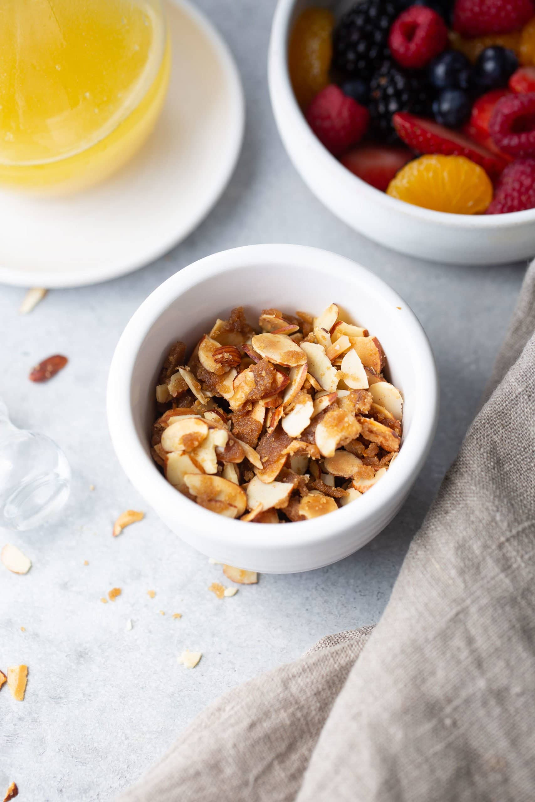 a photo of a small white dish full of brown sugar sliced almonds.
