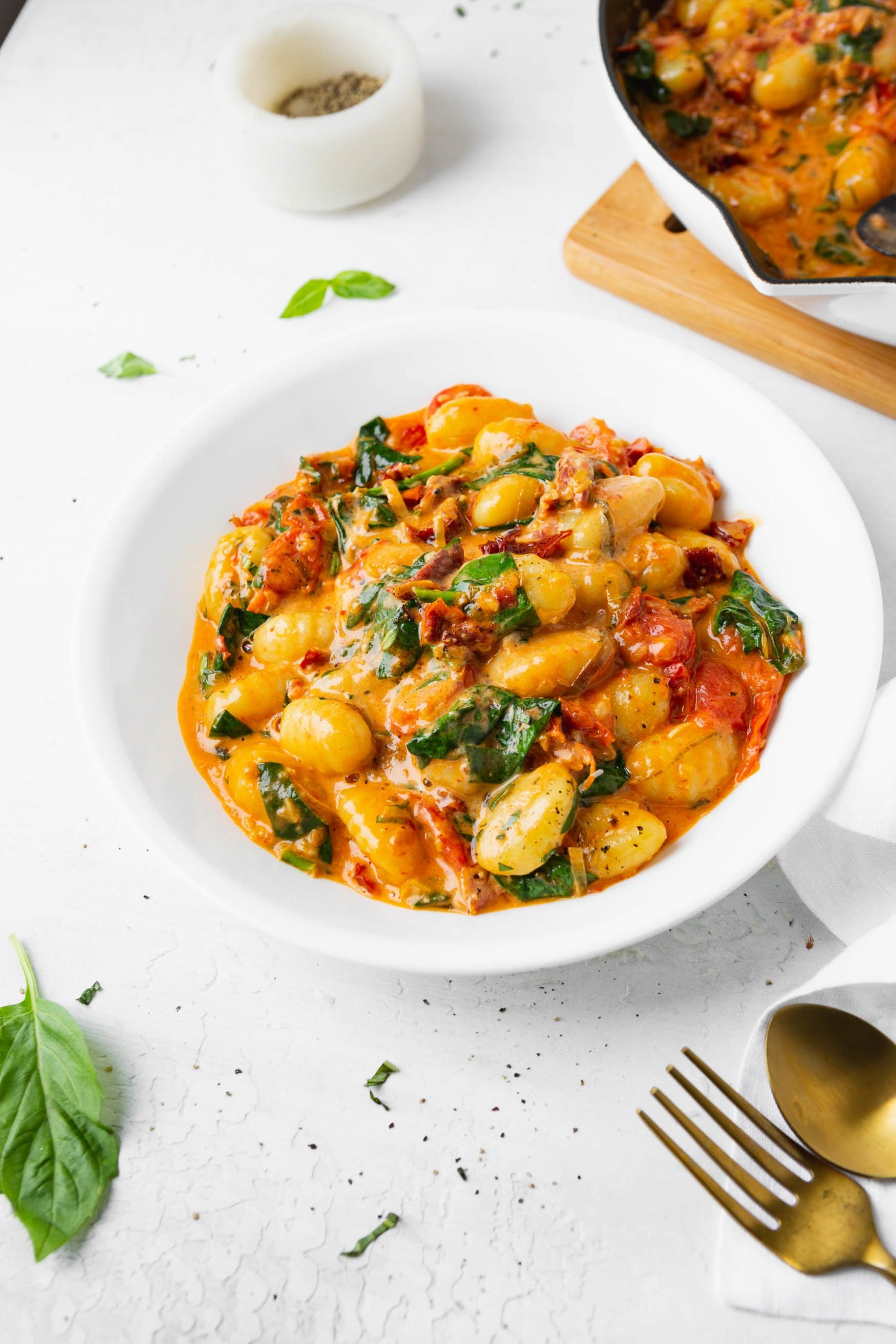 A photo of a white bowl full of creamy sun dried tomato gnocchi with a fork and spoon sitting next to the bowl.