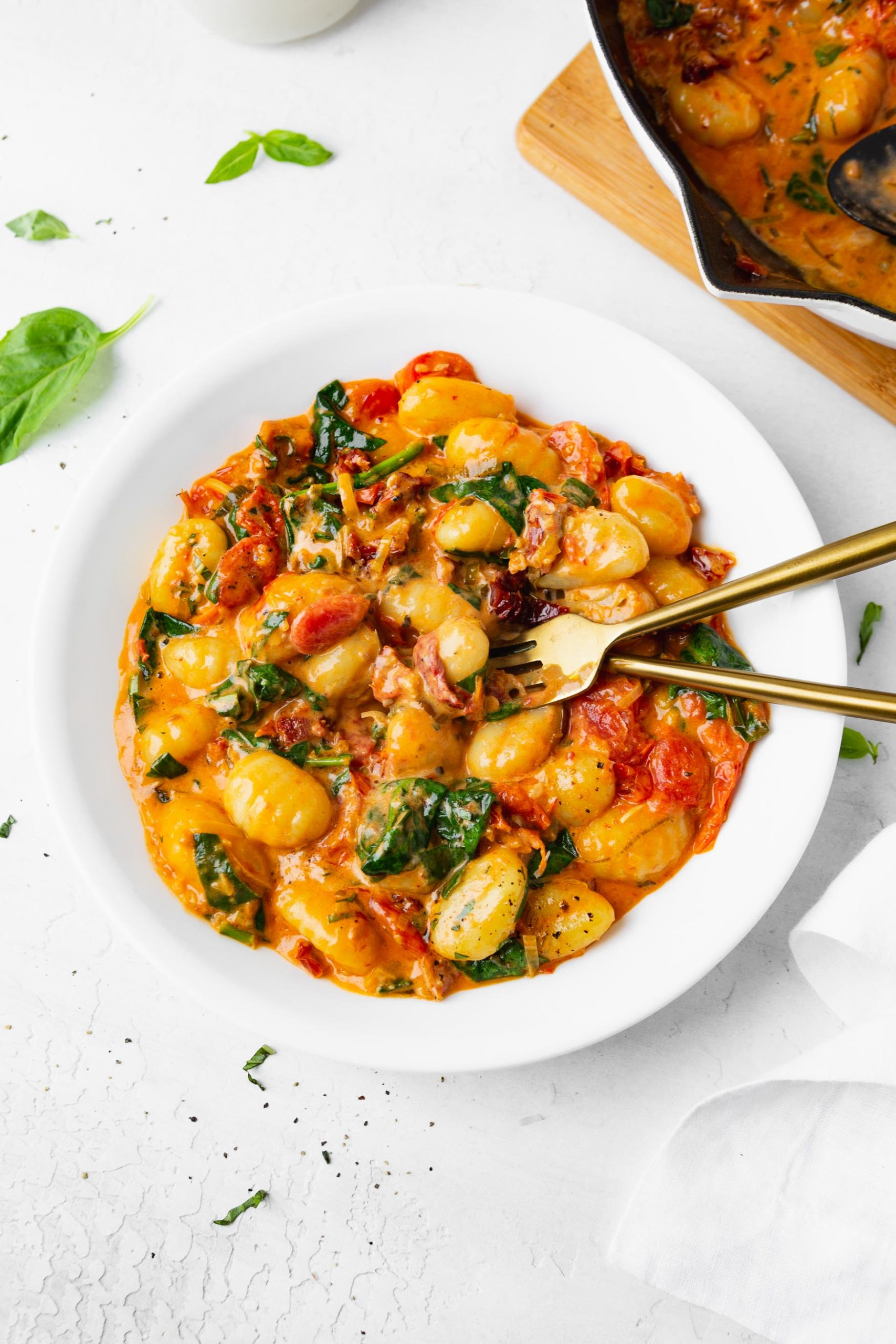 A photo of a white bowl full of creamy sun dried tomato gnocchi with a fork and spoon sitting in the bowl.