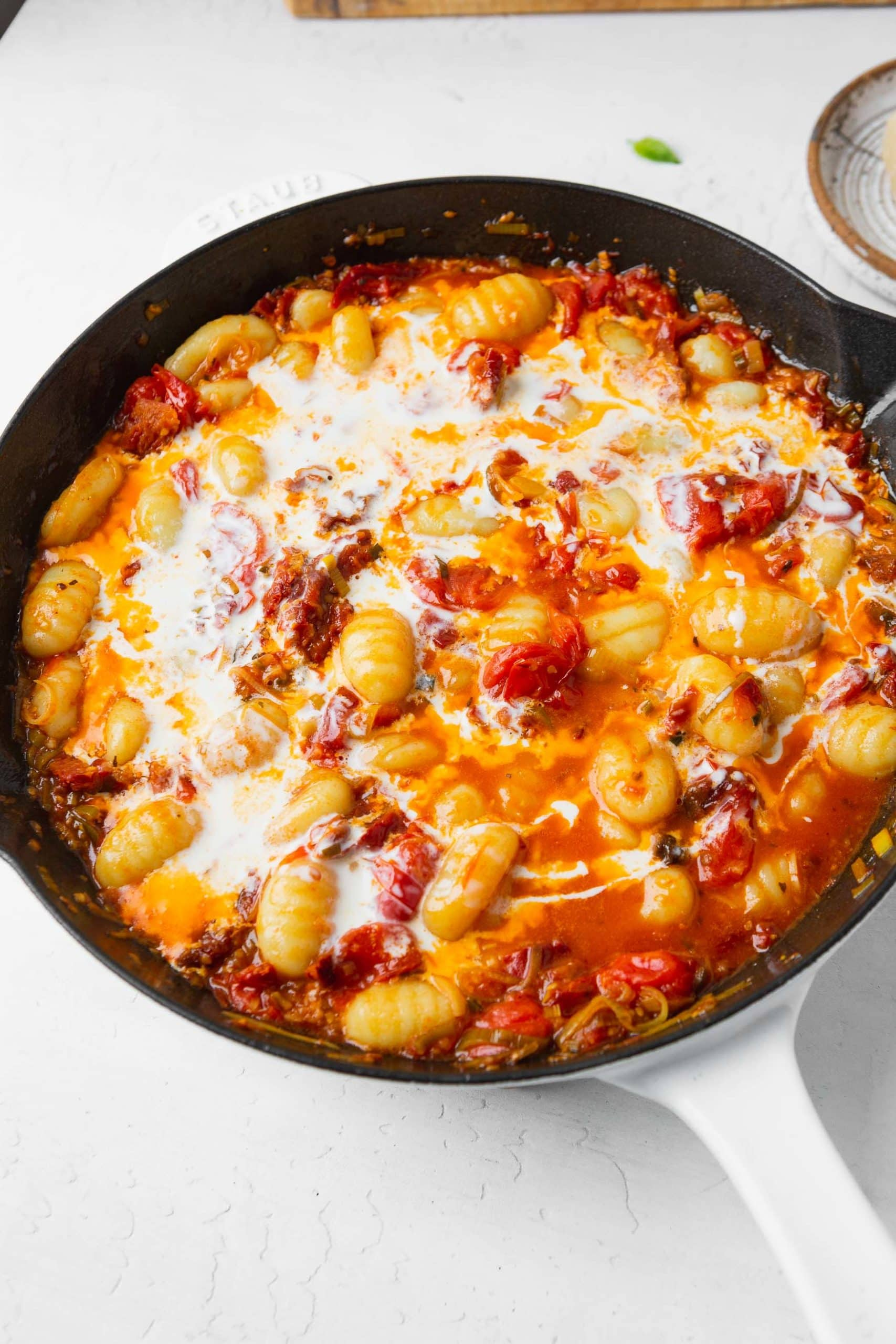 A photo of creamy sun dried tomato gnocci in a cast iron skillet with the gnocchi and cream added.