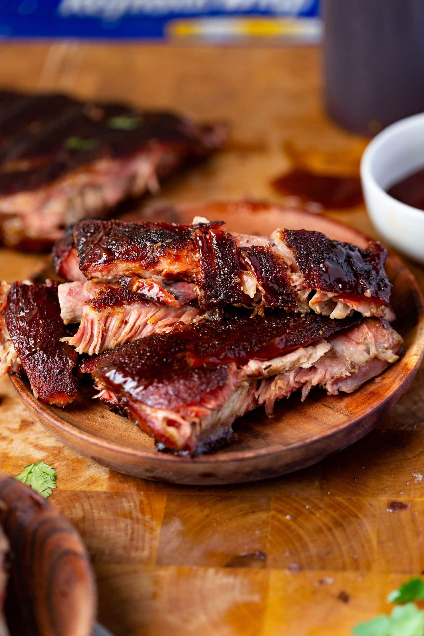 a photo of a wooden plate piled high with juicy ribs.