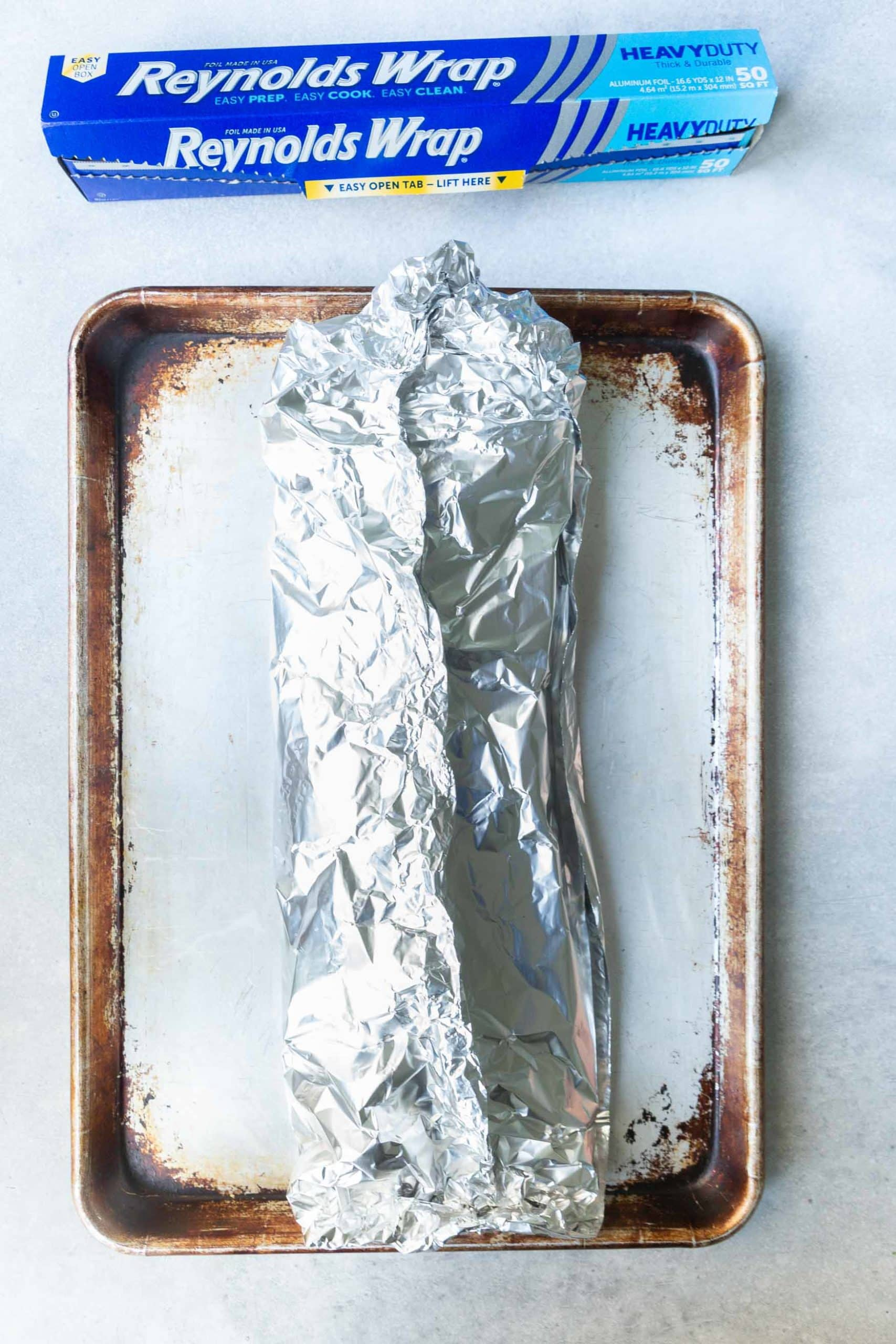 a photo of a baking sheet with a rack of ribs wrapped in foil on it.
