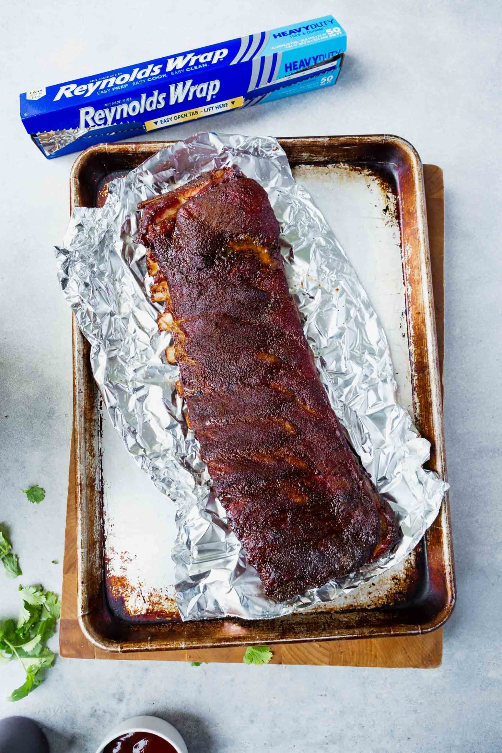 a photo of a grilled rack of ribs sitting on a sheet of foil on top of a baking sheet.