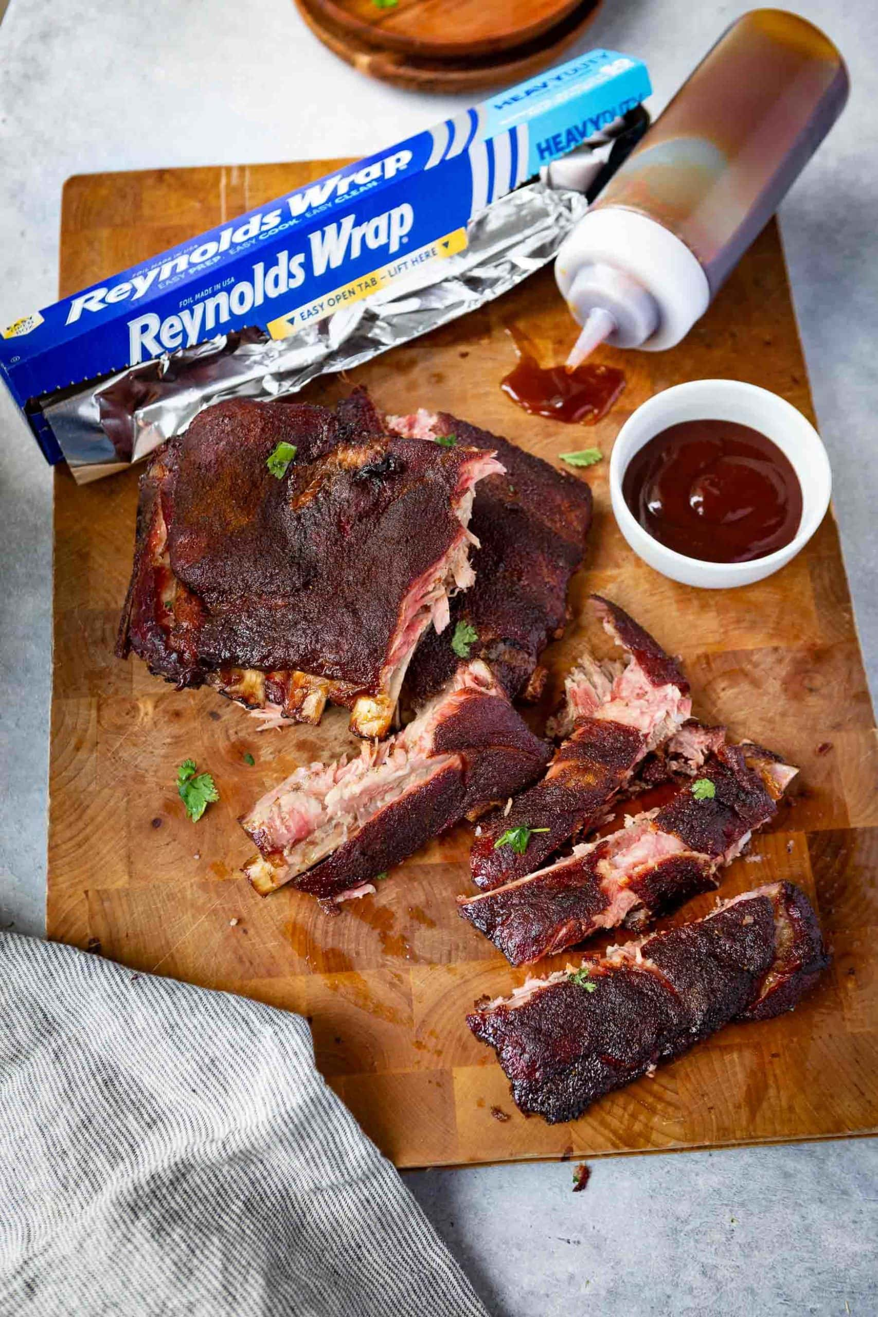 a photo of a rack pf grilled spare ribs broken apart on a wooden cutting board. there is a box of reynolds wrap next to the ribs and a small bowl of bbq sauce on the side as well as a sauce bottle with bbq sauce in it.