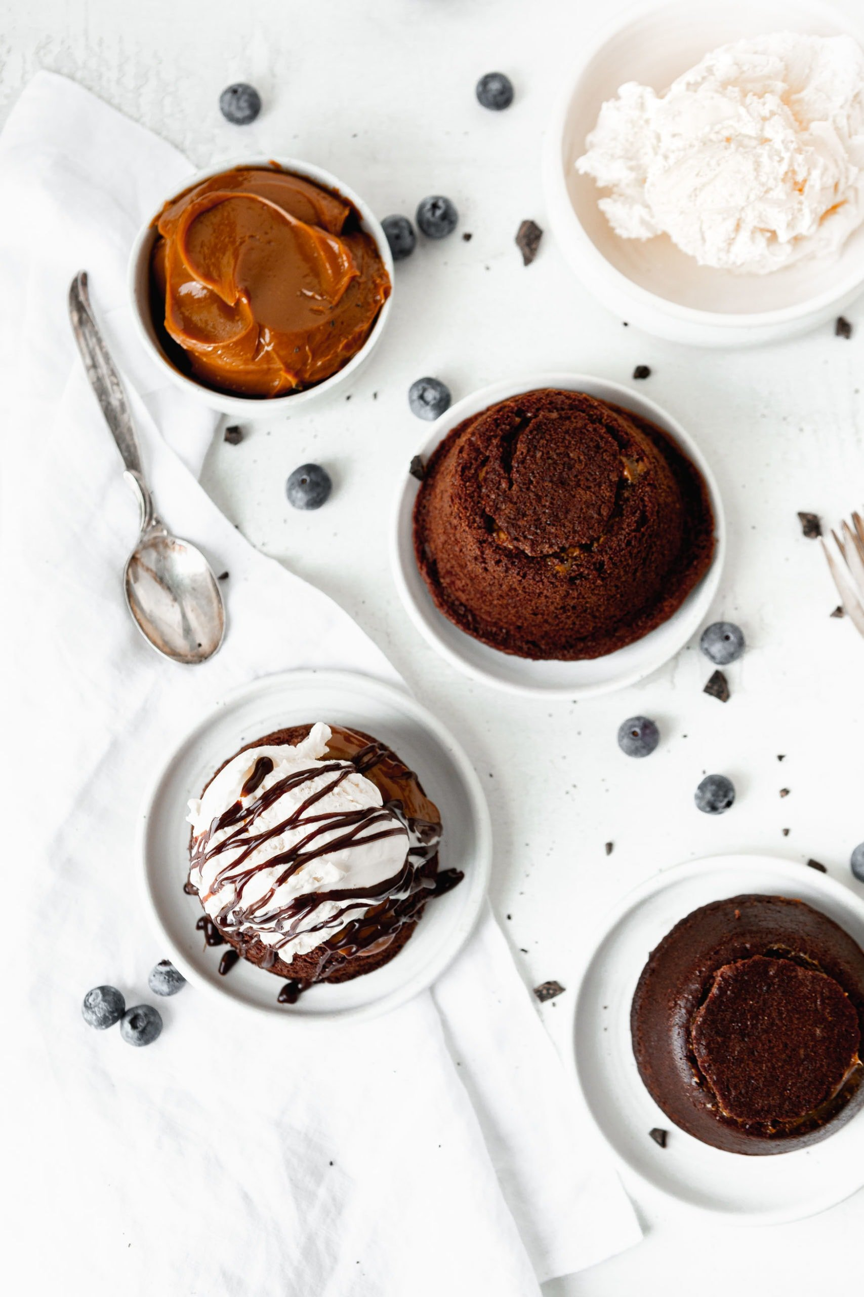 Molten lava cakes on dessert plates. One has been topped with a scoop of ice cream and chocolate drizzles. There are a few blue berries scattered on the table and a spoon is next to a bowl of caramel.