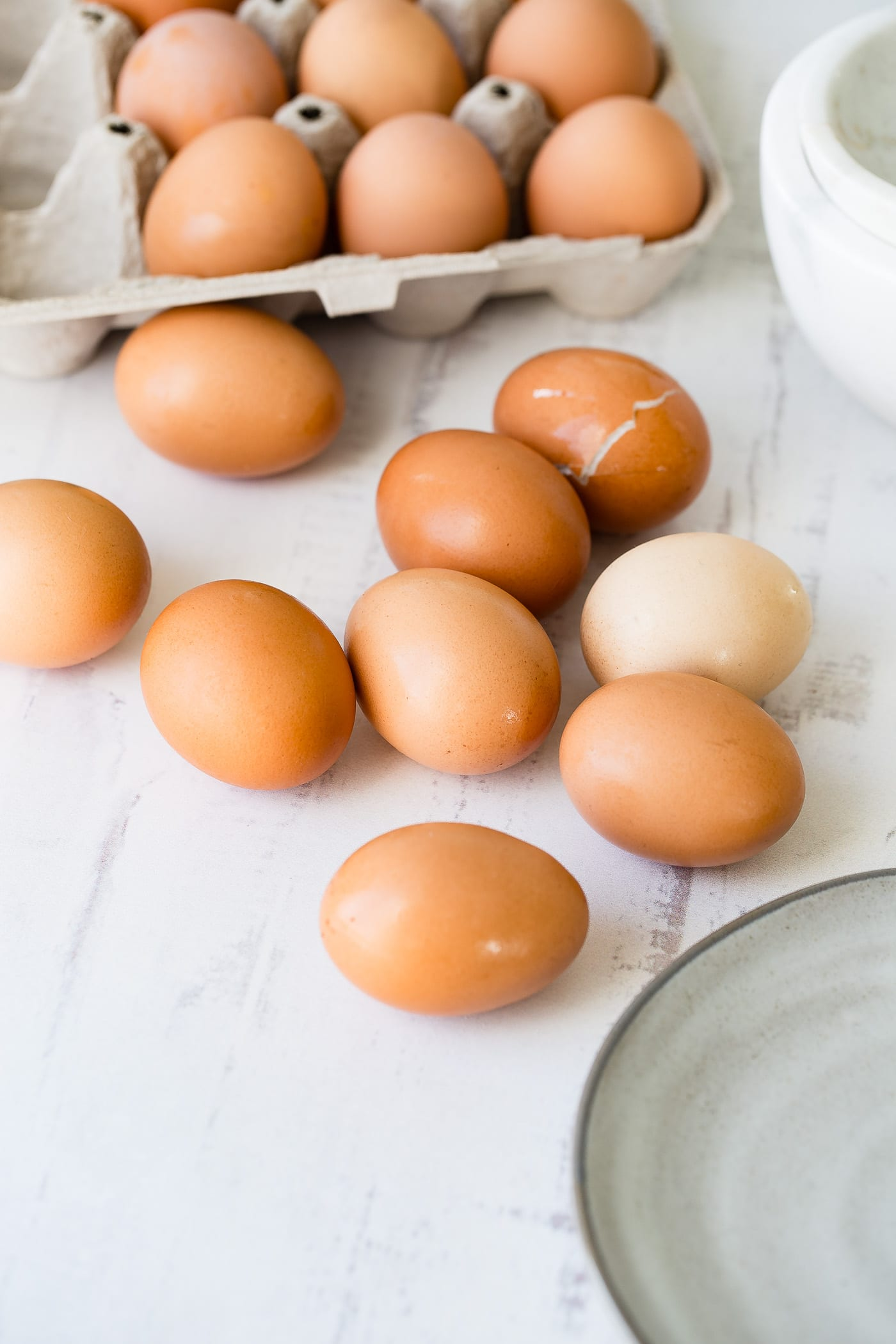 Nine brown eggs laying on a counter top with a carton of brown eggs in the background.