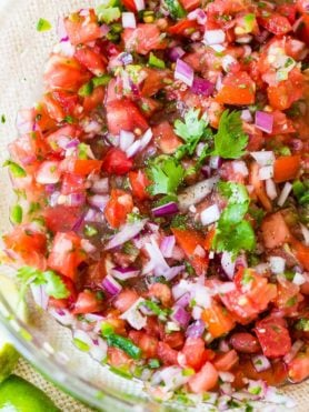 A bowl of pico de gallo complete with tomatoes, red onions, cilantro and jalapenos.