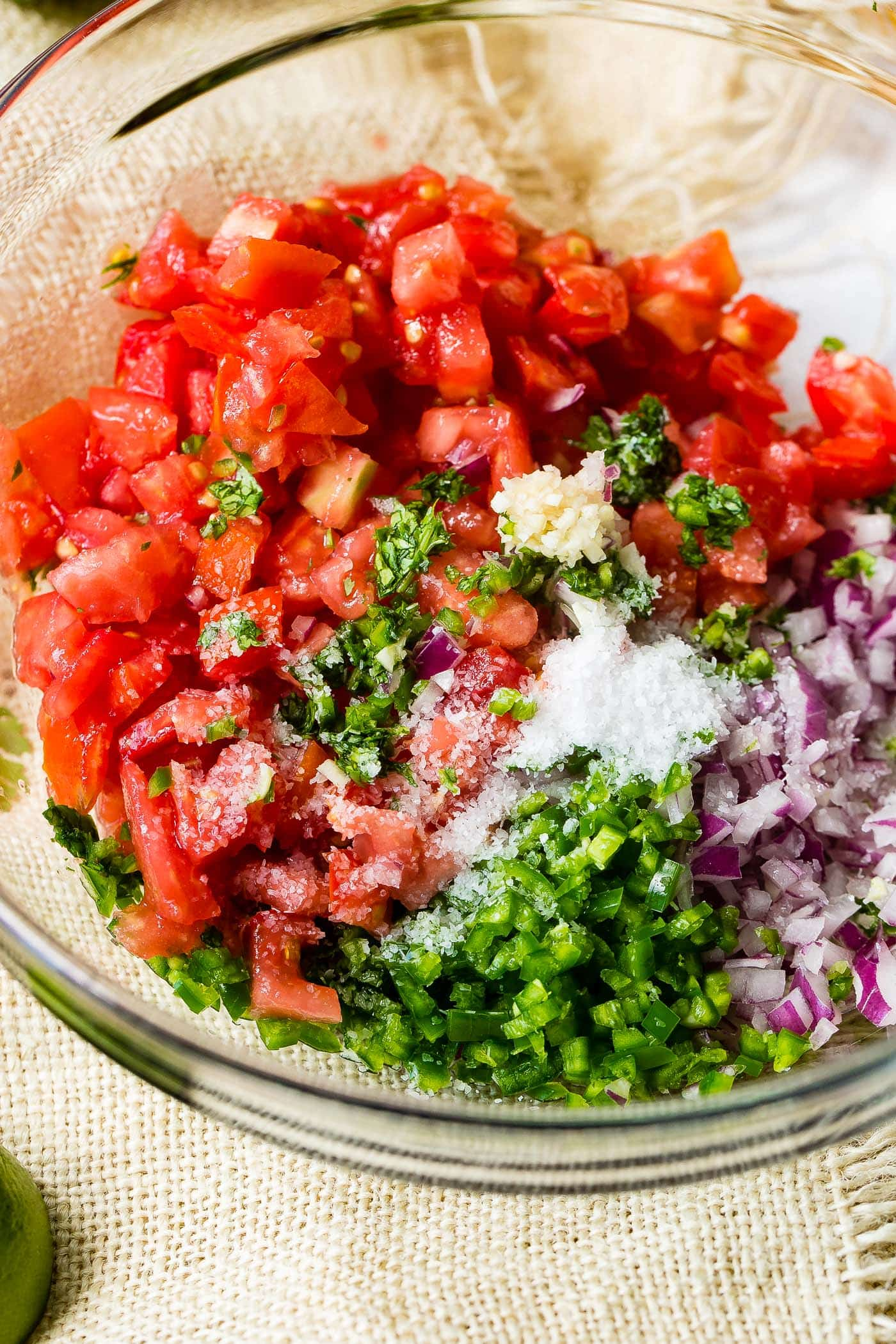 A glass bowl full of all the ingredients for pico de gallo that haven't been stirred together yet.