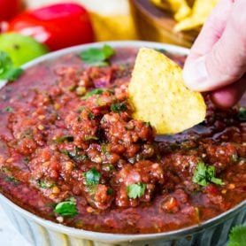 A bowl of homemade salsa in which a tortilla chip is being dipped. The salsa is sprinkled with cilantro leaves and has cilantro and roma tomatoes and a lime in the background. There is also a wooden bowl of chips in the background.