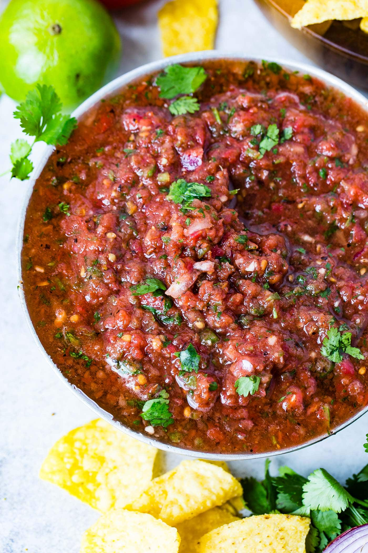 A close-up picture of fresh salsa with chopped tomatoes, jalapenos, onions, spices and cilantro leaves on top.