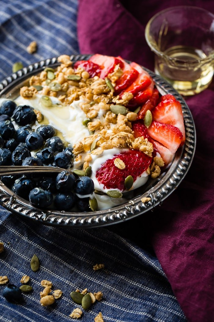 Instant pot yogurt in a vintage bowl with a drizzle of honey and granola with pepitas and fresh blueberries and sliced strawberries for a healthy breakfast recipe