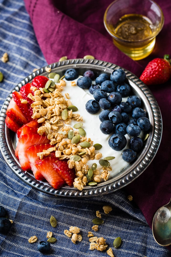 Instant pot homemade yogurt in a vintage bowl with a drizzle of honey and granola with pepitas and fresh blueberries and sliced strawberries for a healthy breakfast recipe