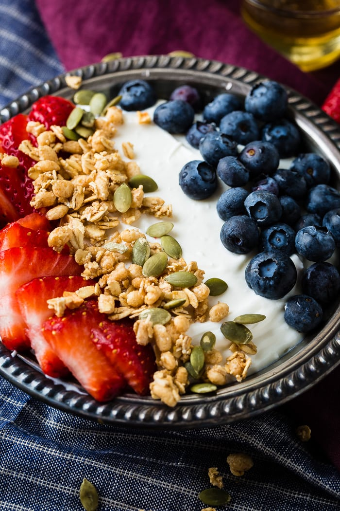 Bowl of instant pot homemade yogurt with fresh blueberries, strawberries, pepitas, granola and a drizzle of honey in a vintage bowl with blue and purple napkins.