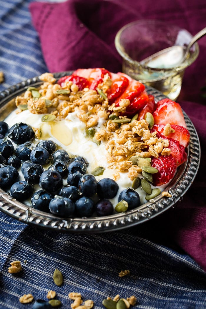 Bowl of instant pot yogurt with fresh blueberries, strawberries, pepitas, granola and a drizzle of honey in a vintage bowl with blue and purple napkins.