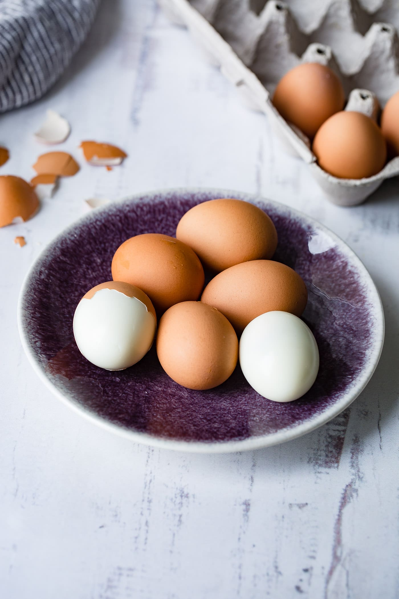 A plate with 6 brown hard boiled eggs. One has been peeled and one is partially peeled. There are brown egg shell and a carton of eggs in the background.