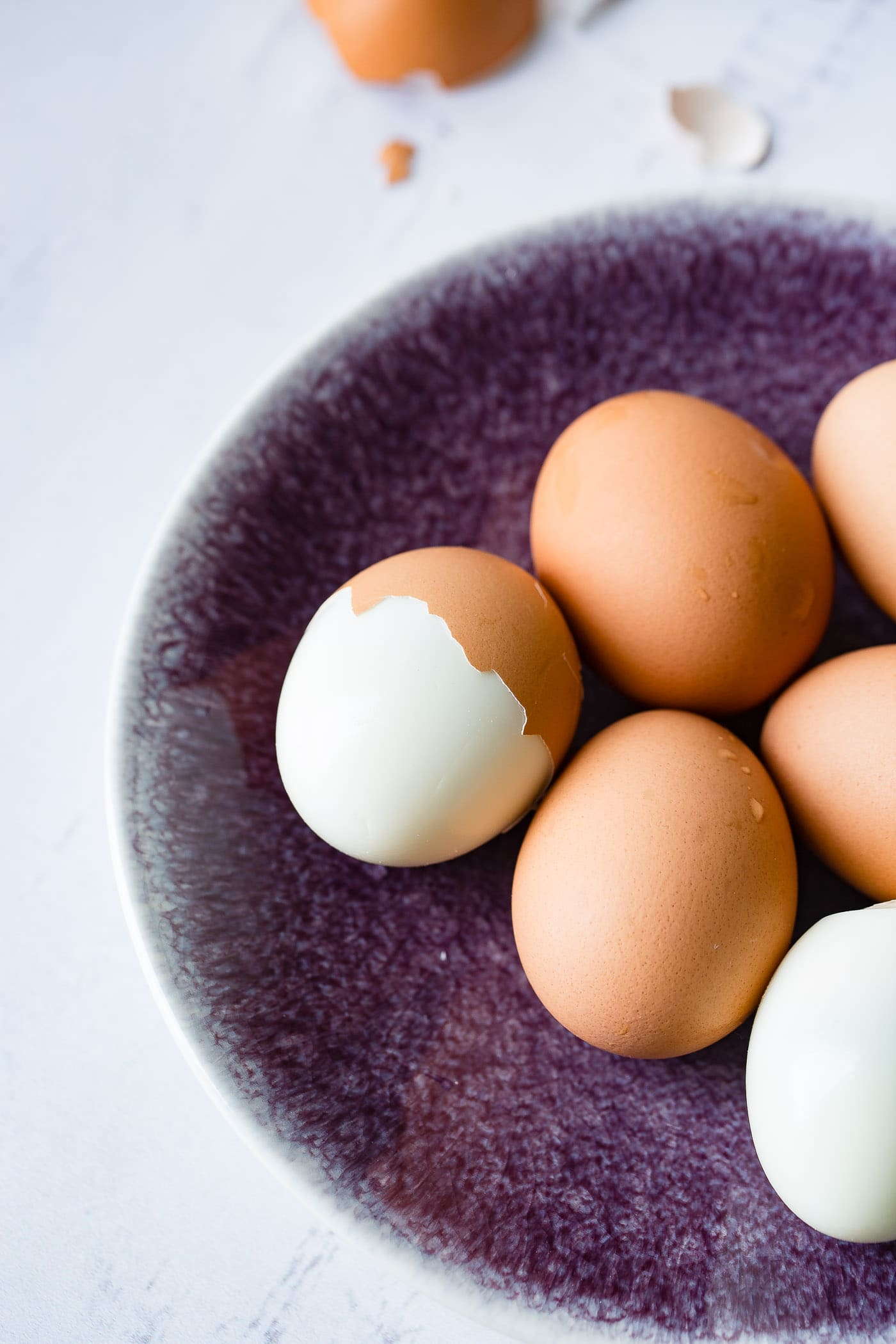 A plate with 6 brown hard boiled eggs. On egg is peeled and another egg is partially peeled.