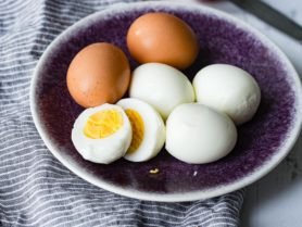 A plate with 6 hard boiled eggs. There are two brown eggs, three that have been peeled and one that is peeled and cut in half with a perfectly cooked yolk. There are two more brown eggs in the background and a blue and white striped cloth on the table.
