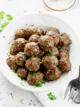 A large bowl of cooked meatballs with chopped parsley sprinkled over the top. A fork and spoon are next to the bowl of meatballs.