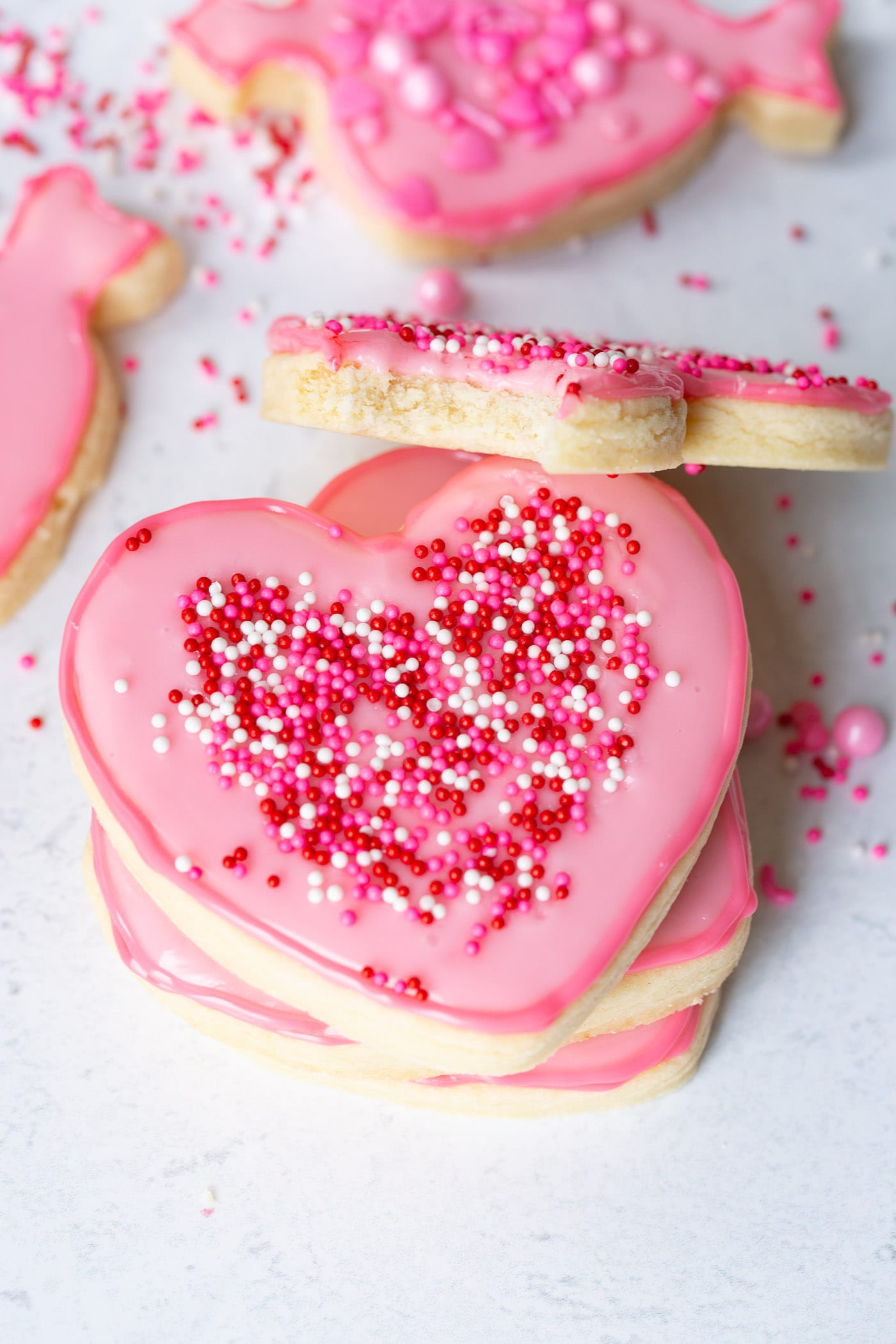 a pink heart sugar cookie with sprinkles