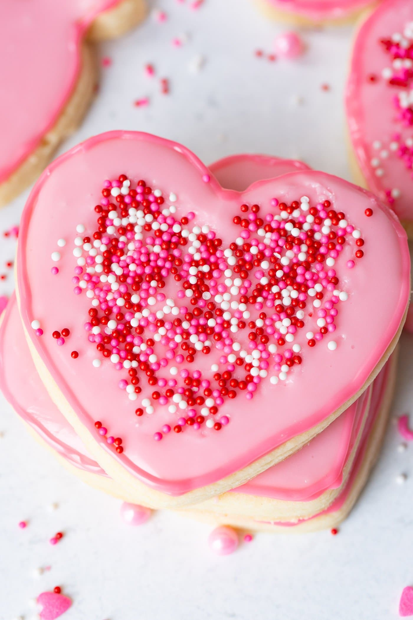 a stack of pink heart cut out sugar cookies with sprinkles on top