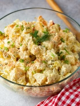 A glass serving bowl of potato salad. There are chunks of potato, chopped eggs, chopped pickles stirred together is a light dressing. The salad is topped with sprinkled paprika and fresh parsley. The bowl of salad is sitting next to a red checked napkin and a wooden spoon.